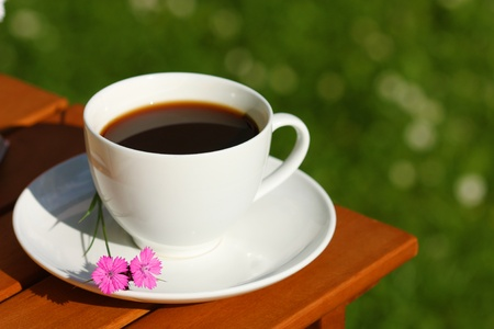 gillyflower: Drinking coffee in the garden. Black coffee in white cup Stock Photo