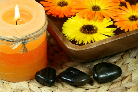 Spa in orange color: candle, calenula flowers and pebbles