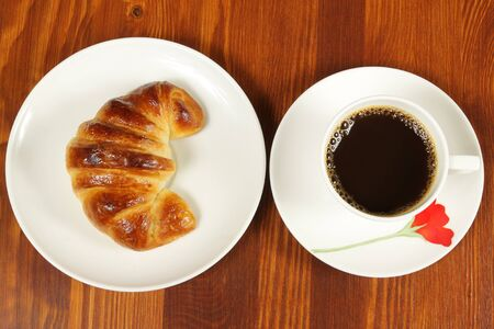 Black coffee and croissant. Breakfast top view photo