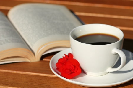time table: Cup of coffee and book in natural garden light Stock Photo