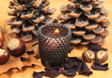 Autumn decoration with chestnuts, candle and cones. Brown colors photo