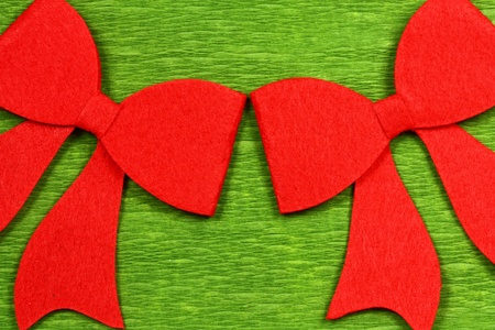 Two red felt bows on green background. Christmas decoration photo