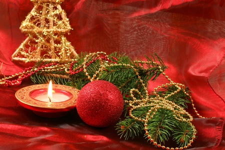Christmas ball, candle and spruce branch - red decoration photo