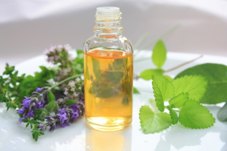 Closeup of oil bottle with fresh green herbs and aromatic flowers. Alternative medicine concept Stock Photo