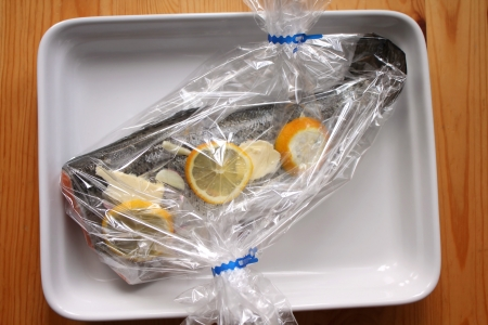 heatproof: Raw trout prepared before baking in oven wrapped in foil
