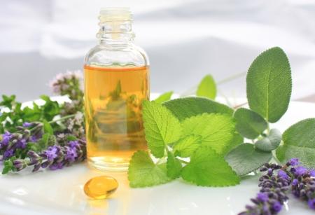 Nahaufnahme von Öl-Flasche mit frischen Kräutern und aromatischen Blumen. Alternative Medizin-Konzept Standard-Bild