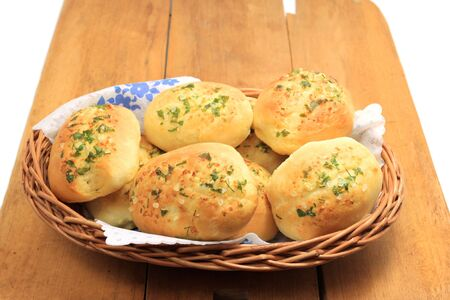 Home made buns with garlic and green parsley in wicker basket photo