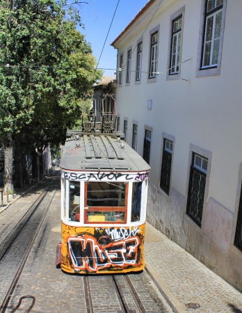 gloria: LISBON, PORTUGAL - SEPTEMBER 10: Yellow tram covered with graffiti on September 10, 2013 in Lisbon Portugal. Yellow tram (funicular) is the symbol and the tourist attraction of Lisbon.
