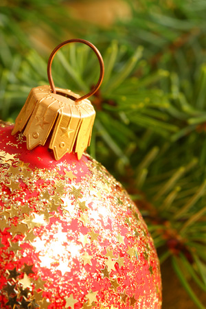 Closeup of red Christmas glass bauble with golden stars.  photo