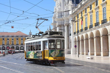 trams: LISBON, PORTUGAL - SEPTEMBER 9, 2013: Yellow tram on Praca do Comercio. Yellow tram (funicular) is the symbol and the tourist attraction of Lisbon. Editorial