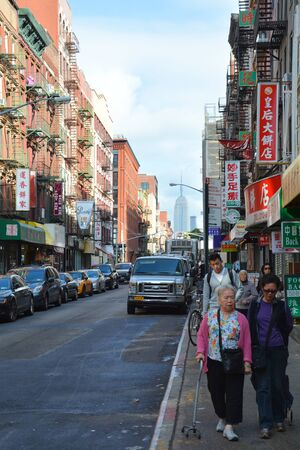 resides: NEW YORK CITY, USA - OCTOBER 14, 2014: People walk on street of Chinatown, Manhattan. This neighborhood resides the largest ethnic Chinese population outside of Asia