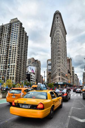 뉴욕 시티, 미국 -20014 년 10 월 18 일 : 맨해튼의 5 번가에서 노란색 택시 및 아이언 빌딩. Flatiron은 뉴욕의 상징적 인 건물입니다.