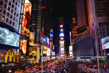 뉴욕시, 미국 - 2014년 10월 17일 : 밤에 타임 스퀘어에 사람들. 타임스 스퀘어 (Times Square)는 세계에서 가장 방문한 관광 명소 중 하나입니다.