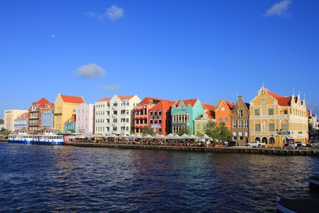 antilles: WILLEMSTAD, CURACAO - FEBRUARY 11,  2014: Waterfront with harbour and colorful houses in Willemstad.  The city centre is UNESCO World Heritage Site.