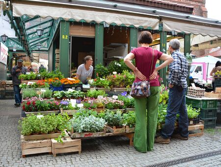 seaports: GDANSK, POLAND - JUNE 27, 2015: People shop at the herbs and flowers stall market in old town. Gdansk has one of the largest seaports on the Baltic Sea