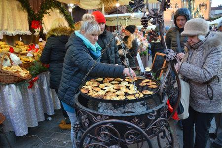 oscypek: KRAKOW, POLAND - DECEMBER 4, 2016:  Christmas market stall with Grilled cheese oscypek.The annual Christmas markert in the Market Square is a popular tourist attraction
