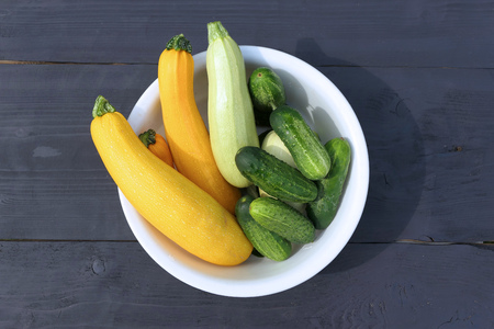 Summer squashes and cucumbers harvest on wooden background. Gourds family