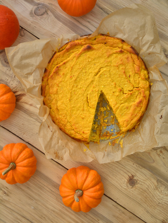 Pumpkin cheesecake. Flat lay composition on wooden background