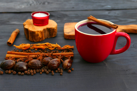 Christmas mulled wine with spices in red mug on wooden background. Cinnamon, nutmeg, star anise, cloves.