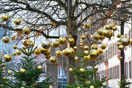 Golden baubles hanging on tree. Christmas town decoration Stok Fotoğraf