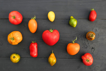 Heirloom tomatoes, different colors and varieties on black wooden background.
