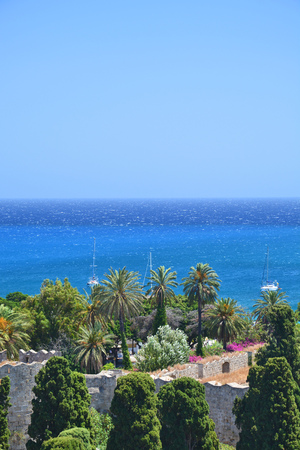 Outdoor landmark view on Rhodes town walls, palm trees and Aegean sea.
