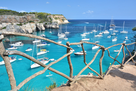 Turquoise water in bay Cala Macarella on Menorca island in Spain. Wooden typical fence. Imagens