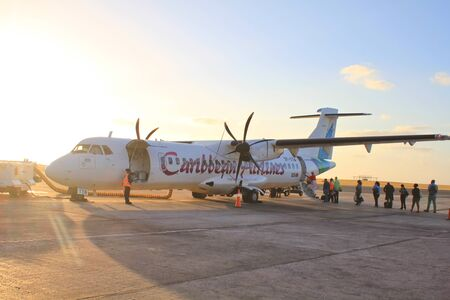 BRIDGETOWN, BARBADOS - FEBRUARY 21, 2014: Caribbean Airlines plane boarding at the airport in Bridgetown and departing to Trinidad and Tobago island.