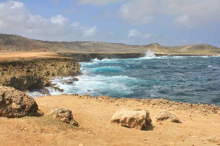 Water waves crashing on the cliffs of Aruba island. Netherland Antilles on Caribbean sea.