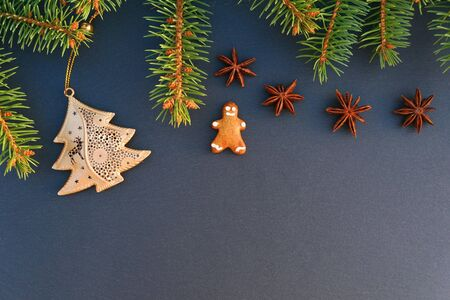 Christmas border made of spruce tree branch, gingerbread man cookie on dark stone board background.