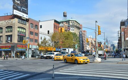NEW YORK CITY, USA - OCTOBER 14, 2014: Landmark of morning city streets with yellow taxi cabs in Chinatown, Manhattan. This neighborhood resides the largest ethnic Chinese population outside of Asia.
