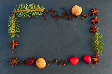 Christmas natural  frame decoration. Spruce branches, spices, walnuts and apples on black stone background. Banco de Imagens