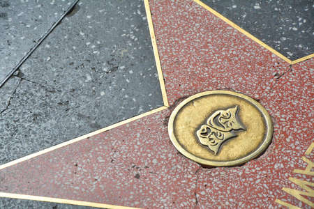 LOS ANGELES, CA, USA - MARCH 27, 2018 : The Hollywood Walk of Fame stars in Los Angeles. Theater or live performance represented by comedy and tragedy masks emblem on the star.