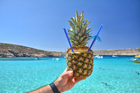 Pineapple fruit refreshing cocktail drink over Lagoon sea waters on Comino island, Malta.