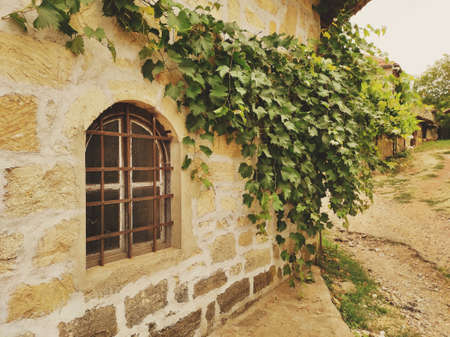 The stone house is overgrown with vines. Old window with metal bars. Stock Photo