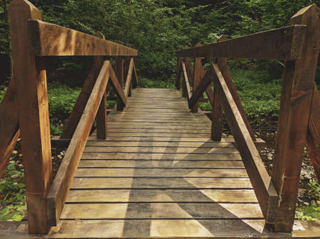 Wooden bridge over a small river. Stock Photo