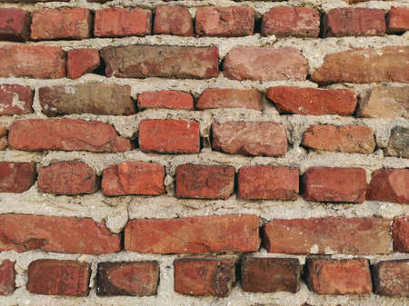 A wall of old bricks that have fallen into disrepair.
