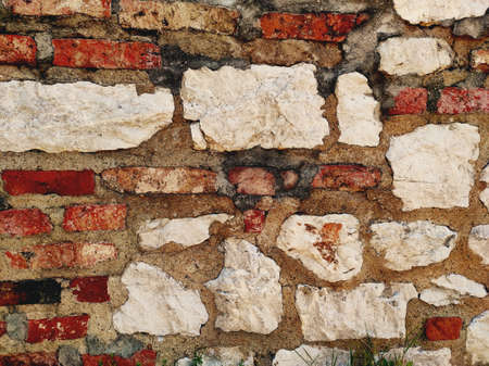 An old wall built of layers of brick and white stone.