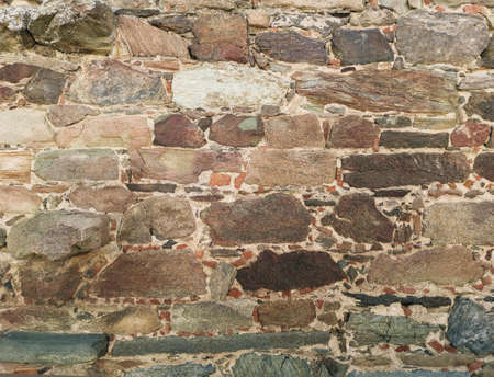 Stari zid od kamena na staroj tvrđavi. Naziru se delovi raznobojnog kamena.