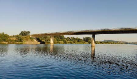 White bridge over calm blue river. The concept of connection.