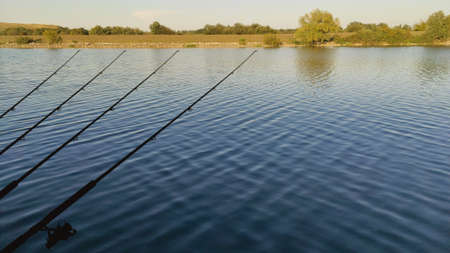 Fishing rods pointing towards the blue river.The concept of fishing.