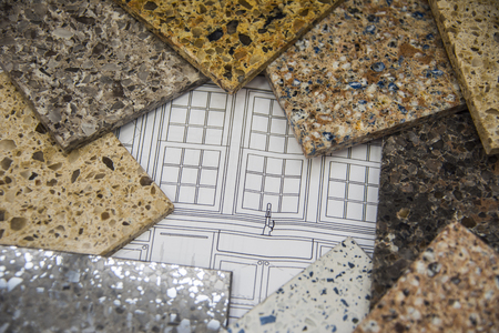 Kitchen countertops and bath counter stone sample colors placed on top of a blueprint layou 스톡 콘텐츠