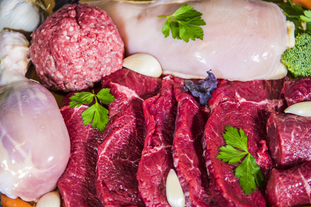 vegtables: Fresh meaton display: Red meat, white poulty meat, lamb meat and ground beef layed out with hints on garlic, broccoli, and parsley leaves scattered on top. Stock Photo