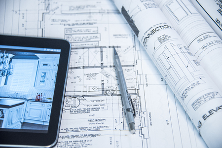 Blueprints rolls set on a work bench with a tablet of designs and a work pen Stock Photo