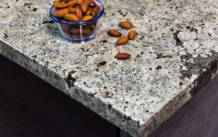 scratches: Nuts on kitchen granite countertop. Counter top made of granite natural stone. Stock Photo