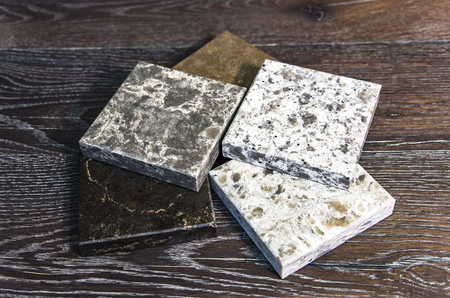 granite color samples on wooden table Stock Photo
