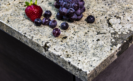 Stone table top (as kitchen island) on blur kitchen background floor - can be used for display or montage your products