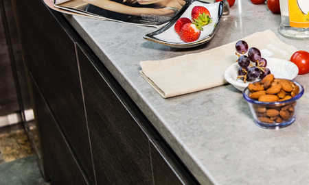 Modern gray kitchen features dark gray flat front cabinets paired with white quartz countertops and a glossy gray linear tile backsplash. Bar style kitchen island with granite counter.