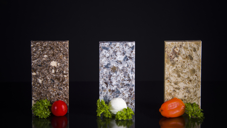 Three stone samples of kitchen cunter tops with food decoration on black table Stock Photo - 82653352