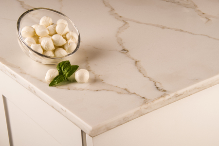 White elegant kitchen marble counter top with italian mozzarela on it, white kitchen cabinets Archivio Fotografico